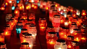 Много красочные свечи горя на кладбище вечером Votive свечи накаляют на могиле Весь день Святого Молитва осветила свечи в a сток-видео