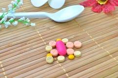 Много красочные таблетка и ложка медицины с цветком Стоковая Фотография RF