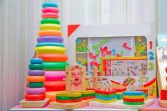 Много красочных деревянных пирамид забавляются на белой предпосылке Строение пирамиды от покрашенных деревянных колец игрушка, де Стоковая Фотография RF