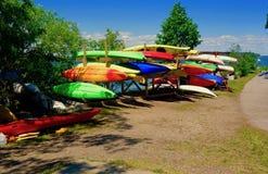 Много красочных каяков хранили outdoors сплавляться гребли шлюпок Стоковые Фото