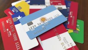 Много кредитных карточек с различными флагами, подчеркнули карту банка с флагом Аргентины иллюстрация штока