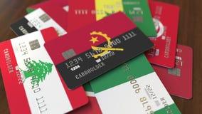 Много кредитных карточек с различными флагами, подчеркнули карту банка с флагом Анголы бесплатная иллюстрация