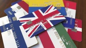 Много кредитных карточек с различными флагами, подчеркнули карту банка с флагом Великобритании бесплатная иллюстрация