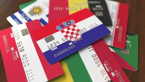Много кредитных карточек с различными флагами, подчеркнули карту банка с флагом Хорватии иллюстрация вектора
