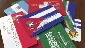 Много кредитных карточек с различными флагами, подчеркнули карту банка с флагом Кубы иллюстрация штока