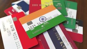 Много кредитных карточек с различными флагами, подчеркнули карту банка с флагом Индии иллюстрация штока