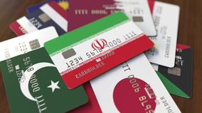 Много кредитных карточек с различными флагами, подчеркнули карту банка с флагом Ирана иллюстрация вектора