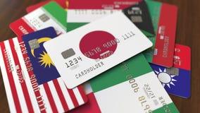 Много кредитных карточек с различными флагами, подчеркнули карту банка с флагом Японии иллюстрация штока