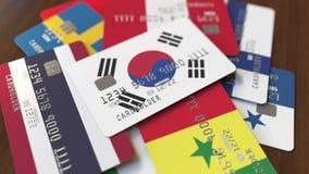 Много кредитных карточек с различными флагами, подчеркнули карту банка с флагом Южной Кореи иллюстрация вектора