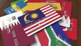 Много кредитных карточек с различными флагами, подчеркнули карту банка с флагом Малайзии иллюстрация штока