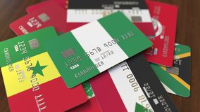 Много кредитных карточек с различными флагами, подчеркнули карту банка с флагом Нигерии иллюстрация штока