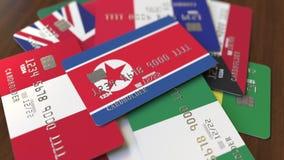 Много кредитных карточек с различными флагами, подчеркнули карту банка с флагом Корейской Северной Кореи иллюстрация штока