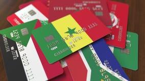 Много кредитных карточек с различными флагами, подчеркнули карту банка с флагом Сенегала видеоматериал