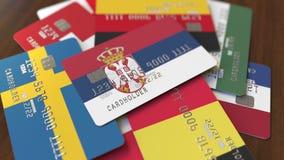 Много кредитных карточек с различными флагами, подчеркнули карту банка с флагом Сербии иллюстрация штока