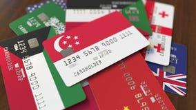 Много кредитных карточек с различными флагами, подчеркнули карту банка с флагом Сингапура видеоматериал