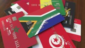 Много кредитных карточек с различными флагами, подчеркнули карту банка с флагом Южной Африки акции видеоматериалы