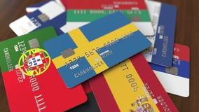 Много кредитных карточек с различными флагами, подчеркнули карту банка с флагом Швеции иллюстрация штока
