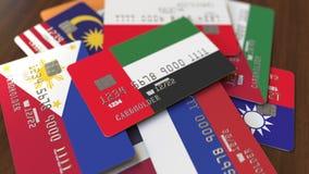 Много кредитных карточек с различными флагами, подчеркнули карту банка с флагом Объениненных Арабских Эмиратов ОАЭ бесплатная иллюстрация