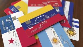 Много кредитных карточек с различными флагами, подчеркнули карту банка с флагом Венесуэлы бесплатная иллюстрация
