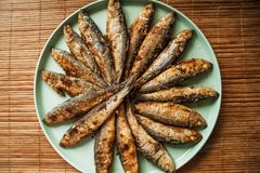 Много малые зажаренные рыбы на большой плите бирюзы Жаркое салата в форме круга лежит, текстура законченных рыб Стоковое Изображение