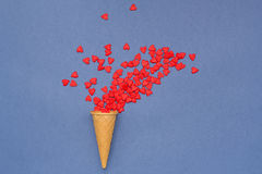 Много малых сердец летая из конуса waffle на голубой предпосылке Стоковая Фотография RF