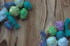 Много малых multicolor шариков хлопчатобумажной пряжи меланжа для вязать, вязание крючком деревянное предпосылки деревенское Стоковые Фото