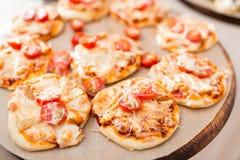 Много мини пицца, на деревянной плите доставка с обслуживанием шведского стола сфокусируйте мягко Стоковые Фотографии RF