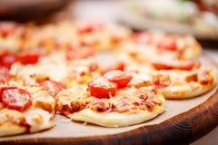 Много мини пицца, на деревянной плите доставка с обслуживанием шведского стола сфокусируйте мягко Стоковые Изображения RF