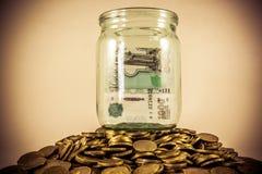 Много монетки и стеклянный опарник стоковые изображения