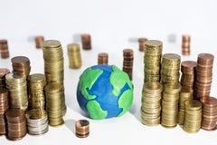 Много монетки на белой таблице с моделью земли Стоковые Фотографии RF
