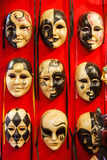 Много отличительных венецианских маск масленицы различных цветов, красной предпосылки Стоковые Изображения