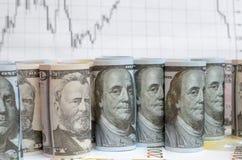 Много переплетенные долларовые банкноты на предпосылке финансовых диаграмм Стоковые Изображения RF