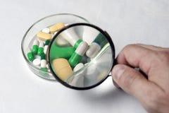 Много пестротканых таблеток Держит лупу в его руке, рассматривая таблетки стоковая фотография