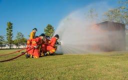 Много пожарный от спасательной команды идет воевать огонь Стоковое Изображение