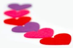 Много покрашенное сердце формирует в ряд стоковое изображение