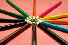 Много покрашенных карандашей на розовой предпосылке Стоковые Изображения
