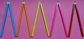 Много покрашенных карандашей на розовой предпосылке Стоковые Фото