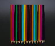 Много покрашенных карандашей на черной предпосылке Стоковые Фотографии RF