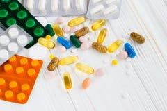 Много покрашенных пилюлек медицины на белой предпосылке Стоковые Фотографии RF
