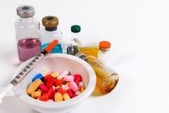 Много покрашенных пилюльки, капсулы и шприца в чашке с ложкой и бутылкой вакцины Стоковые Фотографии RF