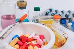 Много покрашенных пилюльки, капсулы и шприца в чашке с ложкой и бутылкой вакцины Стоковая Фотография RF