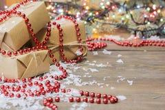 Много подарков ранят бумагу kraft, гирлянду hristmas  Ñ Стоковые Фото