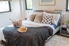 Много подушек на белой кровати в теплой спальне Стоковые Изображения RF