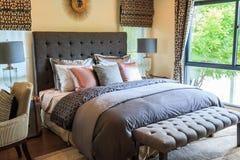 Много подушек на кровати и головные лампы кровати с теплым светом Стоковое Изображение