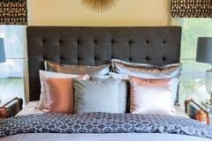 Много подушек на кровати и головных лампах кровати Стоковая Фотография