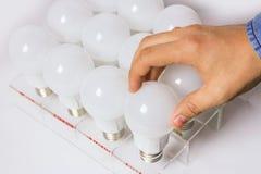 Много привели лампы рука ` s человека вывинчивает электрическую лампочку Стоковое фото RF
