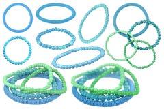 Много примеров голубых и зеленых эластичных браслетов сделанных из похожих на жемчуг круглых шариков и одного голубого металличес стоковое изображение
