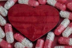 Много различных белых и красных пилюлек r Пилюльки медицины Красное сердце Стоковая Фотография RF