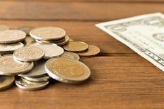 Много различных монеток на деревянном столе с 1 долларовой банкнотой Стоковые Фотографии RF