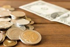 Много различных монеток на деревянном столе с 1 долларовой банкнотой Стоковое фото RF